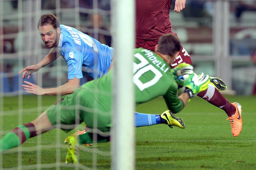 Napoli forward Gonzalo Higuain, left, challenges Torino goalkeeper Daniele Padelli during a Serie A soccer match between at the Olympic  stadium, in Turin, Italy, Monday, March 17, 2014. (AP Photo/ Massimo Pinca)