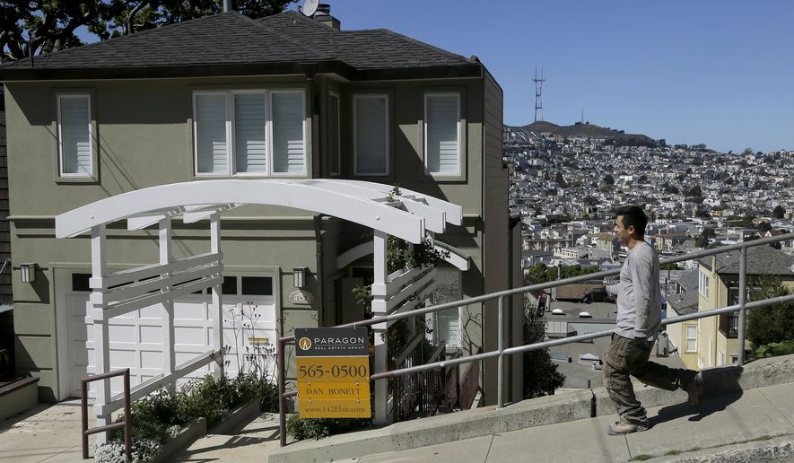A man walks past a home for sale in San Francisco, Monday, March 17, 2014. San Francisco will now lend as much as $200,000 to some homebuyers toward a down payment on their first house or condominium. Mayor Ed Lee's decision to double the previous limit of $100,000 was intended to help middle-class residents who have been hit hard by the housing crunch. (AP Photo/Jeff Chiu)