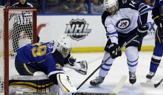 St. Louis Blues goalie Ryan Miller, left, deflects a shot from Winnipeg Jets' Anthony Peluso during the first period of an NHL hockey game Monday, March 17, 2014, in St. Louis. (AP Photo/Jeff Roberson)