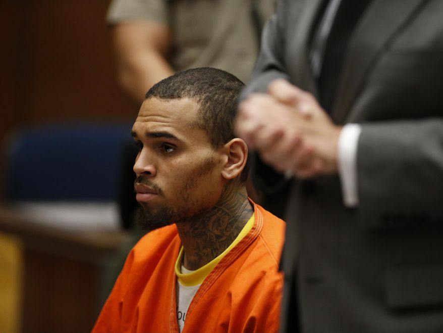 R&B singer Chris Brown, center, appears in Los Angeles Superior Court with his attorney Mark Geragos, right, on Monday, March 17, 2014. Brown will spend another month in jail after a judge said Monday he was told the singer made troubling comments in rehab about being good at using guns and knives. The singer was arrested on Friday, March 14, 2014, after he was dismissed from a Malibu facility where he was receiving treatment for anger management, substance abuse and issues related to bipolar disorder. (AP Photo/Lucy Nicholson, Pool)