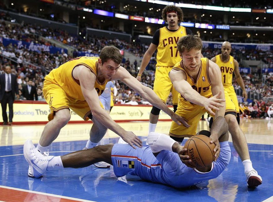 Los Angeles Clippers's Glen Davis, bottom, fights for the ball with Cleveland Cavaliers's Tyler Zeller, left, and Matthew Dellavedova during the first half of an NBA basketball game on Sunday, March 16, 2014, in Los Angeles. (AP Photo/Jae C. Hong)