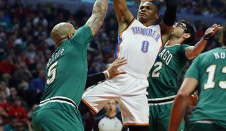 Oklahoma City Thunder guard Russell Westbrook (0) shoots over Chicago Bulls forward Carlos Boozer (5) and Kirk Hinrich, right, during the first half of an NBA basketball Monday, March 17, 2014, in Chicago.  (AP Photo/Jeff Haynes)
