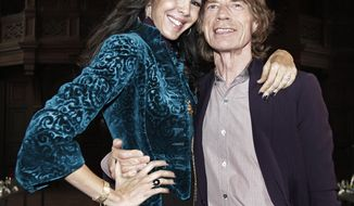 Mick Jagger poses for photos with L'Wren Scott after her Fall 2012 collection was modeled during Fashion Week, in New York,  Thursday, Feb. 16, 2012. (AP Photo/Richard Drew)