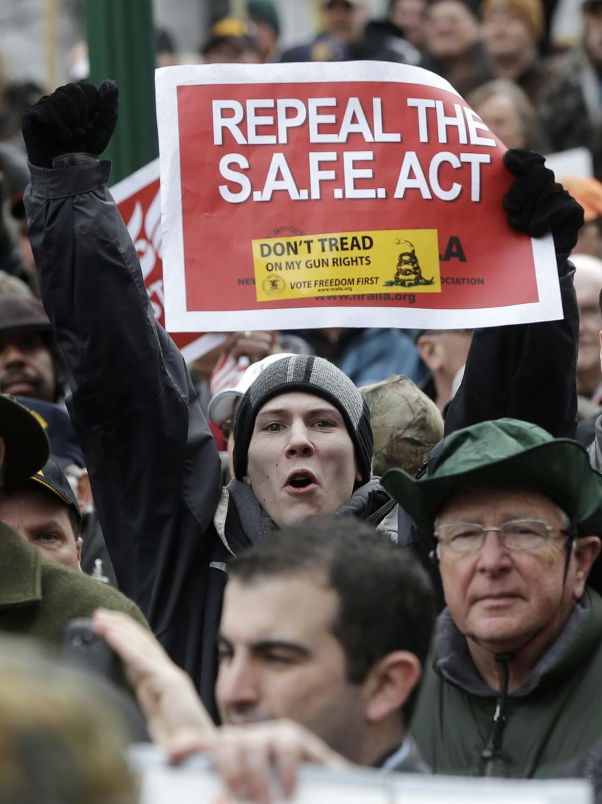 A gun rights advocates holds a sign during a demonstration outside the Capitol on Thursday, Feb. 28, 2013, in Albany, N.Y. The group rallied against the recently legislated NY SAFE Act and other measures they say infringe on their constitutional right to bear arms. (AP Photo/Mike Groll)