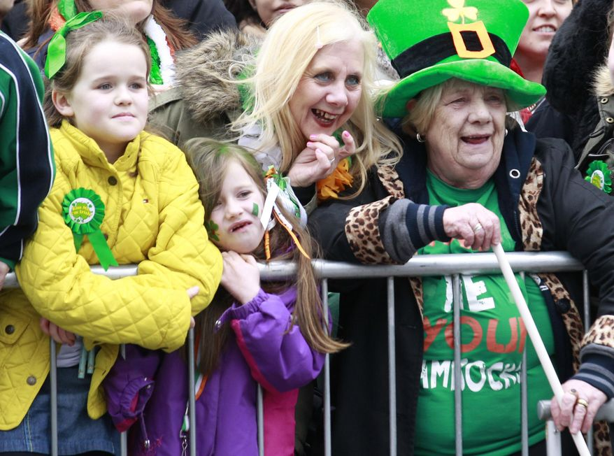 People dress wear fancy dress as they enjoy the atmosphere during the St Patrick's day parade in Dublin, Ireland, Monday March, 17, 2014.  The world's largest parade celebrating Irish heritage set off on a cold and gray morning, the culmination of a weekend of St. Patrick's Day revelry.(AP Photo/Peter Morrison)