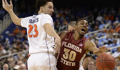 Florida State guard Ian Miller (30) loses control of the ball while guarded by Virginia's London Perrantes (23) during Virginia's 64 to 51 win in an NCAA college basketball game, the third round of the 61st annual Atlantic Coast Conference Basketball on Friday, March 14, 2014, at the Greensboro Coliseum in Greensboro, NC. (AP Photo/Burlington Times-News, Scott Muthersbaugh)