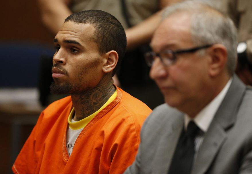 R&B singer Chris Brown, left, appears in Los Angeles Superior Court with his attorney Mark Geragos, on Monday, March 17, 2014. Brown will spend another month in jail after a judge said Monday he was told the singer made troubling comments in rehab about being good at using guns and knives. The singer was arrested on Friday, March 14, 2014, after he was dismissed from a Malibu facility where he was receiving treatment for anger management, substance abuse and issues related to bipolar disorder. (AP Photo/Lucy Nicholson, Pool)
