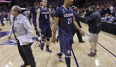 Connecticut's Omar Calhoun (21) and Niels Giffey (5) leave the court after Louisville's 71-61 win in an NCAA college basketball game in the finals of the American Athletic Conference tournament Saturday, March 15, 2014, in Memphis, Tenn.  (AP Photo/Mark Humphrey)