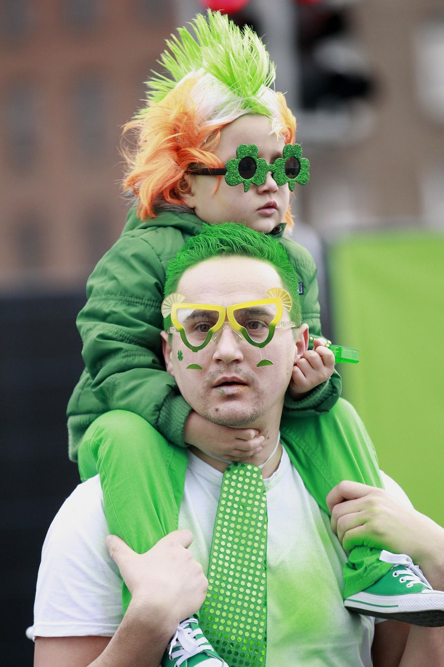 A man and child dressed in emerald green to honour Ireland's Saint Partick, as they enjoy the atmosphere during the St Patrick's day parade in Dublin, Ireland, March, 17, 2014.  The world's largest parade celebrating Irish heritage set off on a cold and gray morning, the culmination of a weekend of St. Patrick's Day revelry. (AP Photo/Peter Morrison)