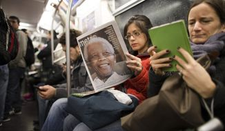 FILE - In this Dec. 6, 2013, file photo, a subway rider in New York reads a newspaper featuring news of the death of South African leader Nelson Mandela. Americans of all ages still pay heed to serious news even as they seek out the lighter stuff, choosing their own way across a media landscape that no longer relies on front pages and evening newscasts to dictate what's worth knowing, according to a new study from the Media Insight Project. (AP Photo/John Minchillo, File)