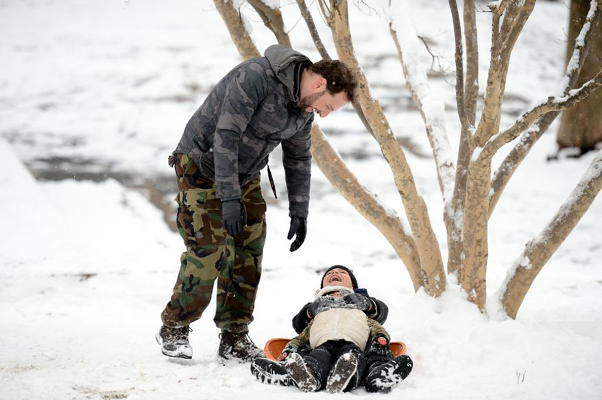 Alberto Otero of Washington, D.C., left, laughs with his two sons Amaro, 7, and Eli, 2, while sledding in Meridian Hill Park as the region gets another snow storm, Washington, D.C., Monday, March 17, 2014. (Andrew Harnik/The Washington Times)