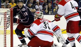 Carolina Hurricanes goalie Anton Khudobin (31), of Kazakhstan, and Andrej Sekera (4), of Slovakia, watch Columbus Blue Jackets' R.J. Umberger's shot go past the net in the second period of an NHL hockey game in Columbus, Ohio, Tuesday, March 18, 2014. (AP Photo/Paul Vernon)