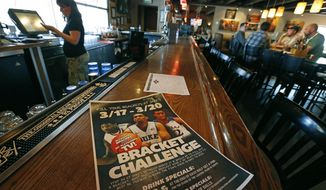 """A poster advertises the """"Bracket Challenge,"""" whereby patrons can complete  an NCAA basketball tournament bracket, at Jake's sports bar, in Denver, Monday March 17, 2014. Warren Buffett has promised a billion dollars for a perfect NCAA bracket, the chances of which are astronomically small. The March Madness, the NCAA tournament is to begin Tuesday. (AP Photo/Brennan Linsley)"""