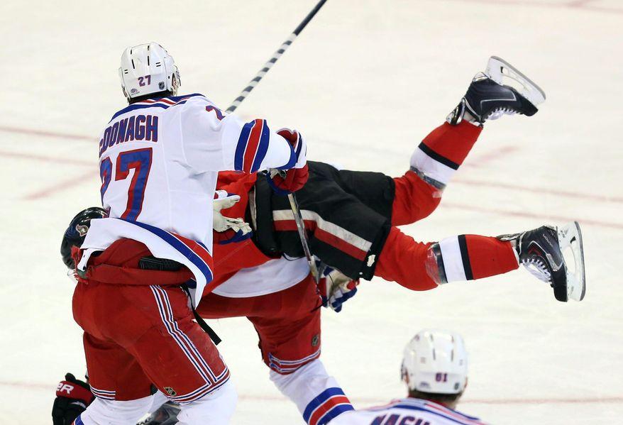 New York Rangers' Ryan McDonagh (27  )dumps Ottawa Senators' Kyle Turris (7) during first period NHL hockey action in Ottawa, Ontario, Tuesday March 18, 2014.  (AP Photo/The Canadian Press, Fred Chartrand)