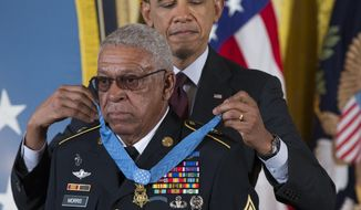 Staff Sgt. Melvin Morris is awarded the Medal of Honor by President Barack Obama during a ceremony in the East Room of the White House in Washington, Tuesday, March 18, 2014. President Obama awarded 24 Army veterans the Medal of Honor for conspicuous gallantry in recognition of their valor during major combat operations in World War II, the Korean War and the Vietnam War. (AP Photo/ Evan Vucci)