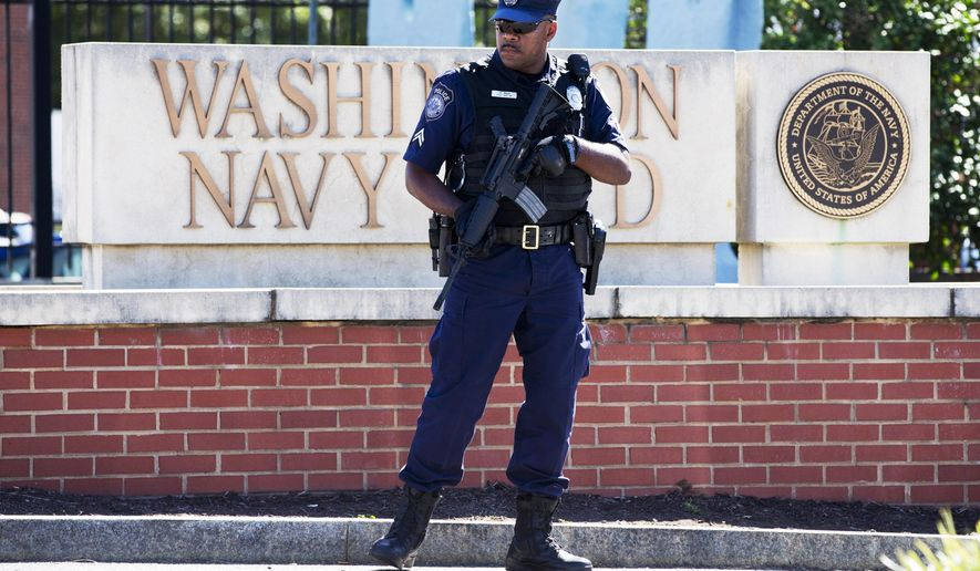 FILE - This Sept. 17, 2013 file photo shows an armed officer who said he is with the Defense Department, standing near guard the gate at the Washington Navy Yard the day after a gunman launched an attack inside the Yard. An independent review triggered by the Washington Navy Yard killings last year says threats to Defense Department personnel and facilities increasingly are coming from within. It says the department must rethink its outdated security theory that suggests defending the perimeters can keep threats away. Instead, it says that terrorism, espionage and even physical threats are coming from trusted insiders. (AP Photo/Jacquelyn Martin, File)