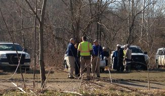 Officials prepare clean-up materials at the scene of a leak from a crude oil pipeline on Tuesday, March 18, 2014, in Colerain Township, Ohio. A Colerain Township fire official said the leak has been contained and that there is no immediate danger to the public. Capt. Steve Conn told The Cincinnati Enquirer oil leaked into a creek and collected in a marshy wetland, and it wasn't clear whether it reached ponds and the Great Miami River. (AP Photo/The Cincinnati Enquirer, Gary Landers)  MANDATORY CREDIT;  NO SALES