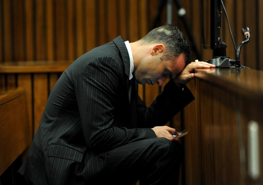 Oscar Pistorius, checks his mobile phone as he sits in the dock waiting for the proceedings of his murder trial to begin in court in Pretoria, South Africa, Tuesday, March 18, 2014. Pistorius is on trial for the murder of his girlfriend Reeva Steenkamp on Valentines Day, 2013. (AP Photo/Werner Beukes, Pool)