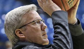 Iowa head coach Fran McCaffrey tosses a ball in during practice for an NCAA college basketball tournament game, Tuesday, March 18, 2014, in Dayton, Ohio. Iowa plays Tennessee Wednesday evening in a first round game. (AP Photo/Al Behrman)