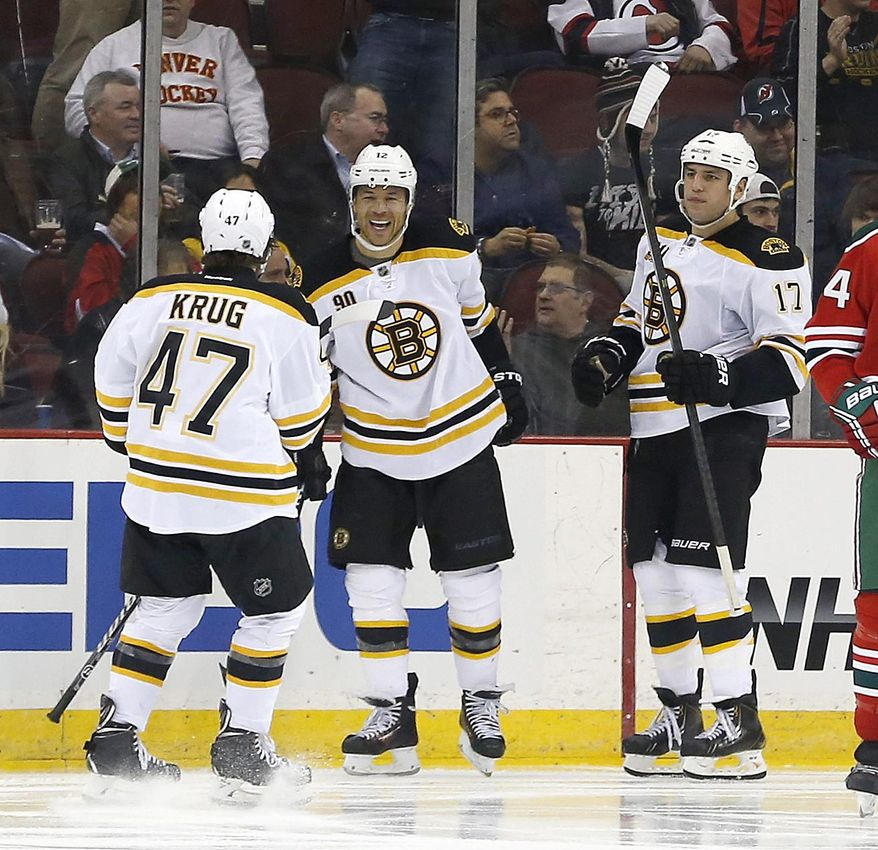Boston Bruins defenseman Torey Krug (47), right wing Jarome Iginla (12) and left wing Milan Lucic (17) celebrate a goal by Iginla against the New Jersey Devils during the second period of an NHL hockey game, Tuesday, March 18, 2014, in Newark, N.J. (AP Photo/Julio Cortez)