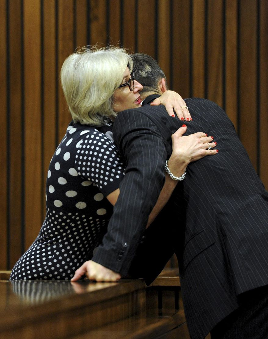 Oscar Pistorius, is greeted by his aunt Lois Pistorius, in court in Pretoria, South Africa, Tuesday, March 18, 2014. Pistorius is on trial for the murder of his girlfriend Reeva Steenkamp on Valentines Day, 2013. (AP Photo/Werner Beukes, Pool)