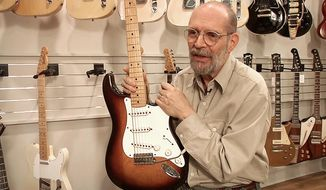 George Gruhn poses with the first production model Fender Stratocaster guitar, Tuesday, March 18, 2014, in Nashville, Tenn. The sunburst-finish Strat bears the serial number 0100. Although some Strats have lower numbers that begin with 0001, Gruhn says they actually were manufactured later in that first year of production. (AP Photo/Kristin M. Hall)