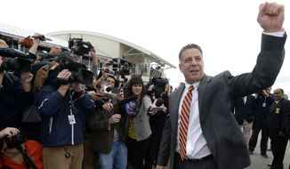 Auburn's new men's basketball coach, Bruce Pearl, gestures and talks to fans upon his arrival Tuesday, March 18, 2014, at Auburn University Regional Airport in Auburn, Ala. (AP Photo/AL.com, Julie Bennett) MAGS OUT