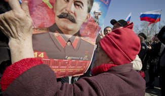 An elderly woman holds a calendar depicting Soviet leader Josef Stalin while watching a broadcast of Russian President Vladimir Putin's speech on Crimea in Sevastopol, Crimea, Tuesday, March 18, 2014, as thousands of pro-Russian people gathered to watch the address. Fiercely defending Russia's move to annex Crimea Putin said Russia had to respond to what he described as a western plot to take Ukraine into its influence.(AP Photo/Vadim Ghirda)
