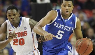 Kentucky guard Andrew Harrison (5) runs on Florida guard Michael Frazier II (20) during the first half of an NCAA college basketball game in the Championship round of the Southeastern Conference men's tournament, Sunday, March 16, 2014, in Atlanta. (AP Photo/Steve Helber)