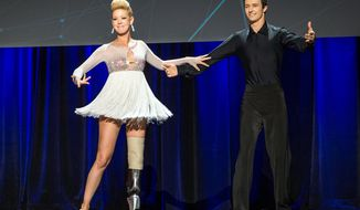 In this photo provided by TED 2014 Conference, dancer Adrianne Haslet-Davis, left, performs on stage with dancer Christian Lightner at the 2014 TED Conference, Wednesday, March 19, 2014, in Vancouver, British Columbia. Haslet-Davis took to the stage with a new prosthetic limb to perform for the first time since losing part of her left leg in the 2013 Boston Marathon bombing. (AP Photo/TED 2014 Conference, James Duncan Davidson)