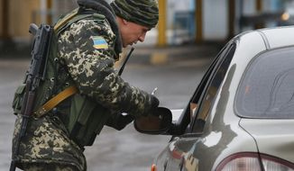 A Ukrainian officer checks documents at the border crossing of Uspenka on the Ukrainian-Russian border, eastern Ukraine, Wednesday, March 19, 2014. Ukraine's leadership simmered with a mix of hopelessness and anger at losing Crimea, tempering an influx of eager young men signing up as reservists with the growing certainty that no savior would deliver them from the Russian takeover. (AP Photo/Sergei Grits)