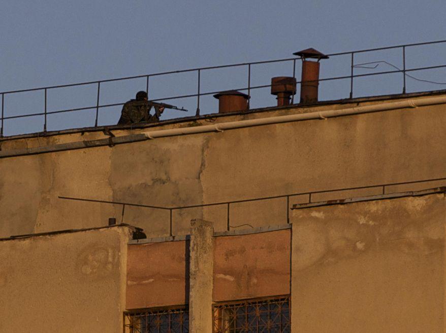 An armed man clears a roof of an Ukrainian military unit in Simferopol, Crimea, on Tuesday, March 18, 2014. (AP Photo/Ivan Sekretarev)