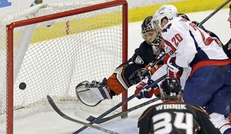 Washington Capitals right winger Troy Brouwer (20) scores on a wrist shot past Anaheim Ducks goalie Jonas Hiller (1), of Switzerland, and center Daniel Winnik (34) in the first period of an NHL hockey game Tuesday, March 18, 2014. (AP Photo/Reed Saxon)