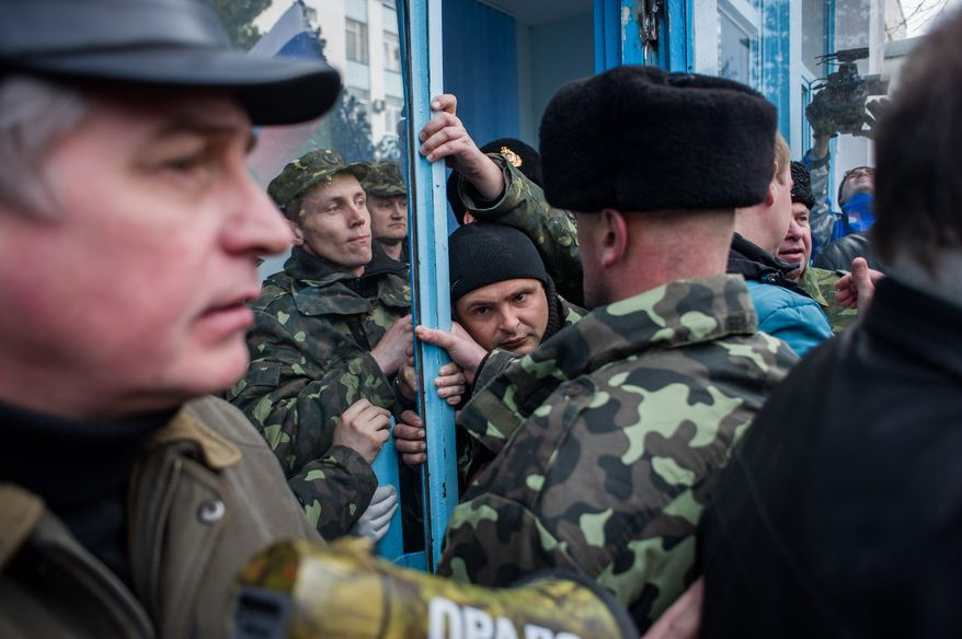 Ukrainian servicemen struggle to defend the navy headquarters in Crimea. Story, A10. (Associated Press)