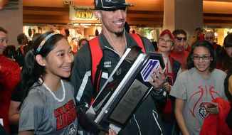 Kendall Williams holds tight onto the Mountain West Tournament Trophy as he poses for a photo with Zoe Benalli, 14, of Shiprock, NM, as the Lobo Basketball team arrives at the Albuquerque International Sunport Sunday Morning, March 16, 2014. The Lobos won the Mountain West tournament in Las Vegas on Saturday. (AP Photo/Albuquerque Journal, Greg Sorber)