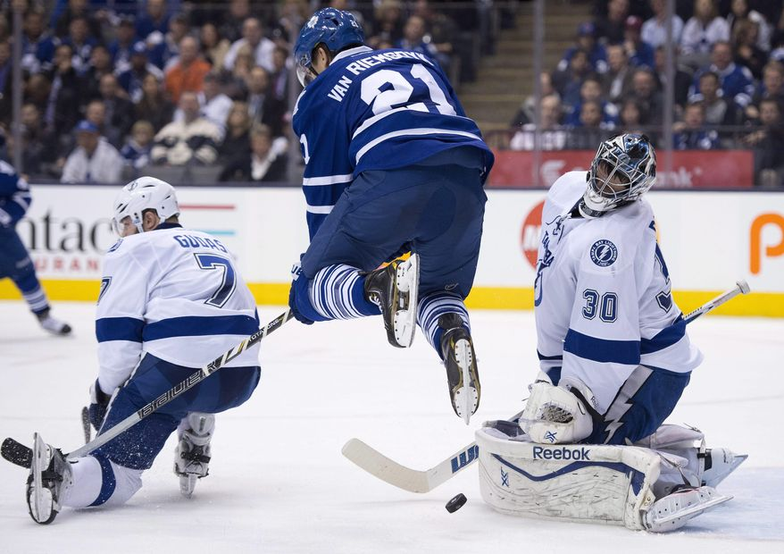 Tampa Bay Lightning goaltender Ben Bishop makes a save as he is screened by leaping Toronto Maple Leafs left winger James van Riemsdyk (21) and defenseman Radko Gudas (7) during second period NHL action in Toronto on Wednesday March 19, 2014. (AP Photo/The Canadian Press, Frank Gunn)