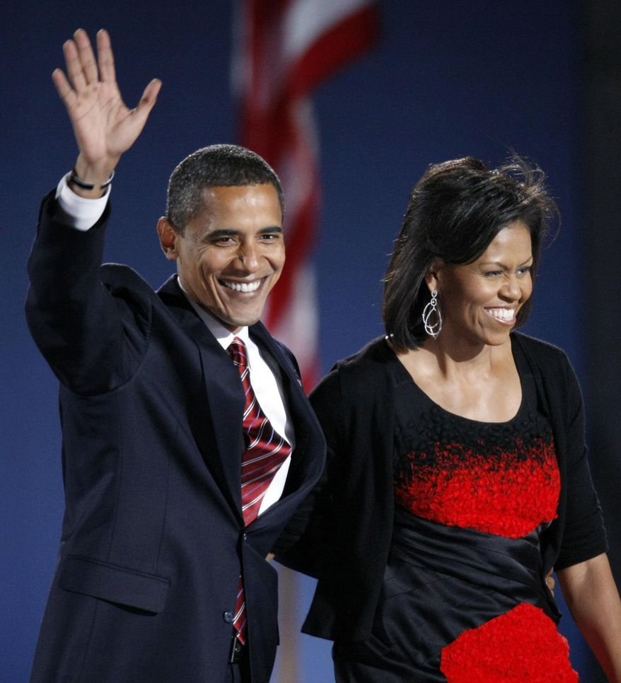 FILE -  In this Nov. 4, 2008 file photo, then-President-elect Barack Obama and his wife Michelle Obama, wearing a Narciso Rodriguez dress, acknowledge the crowd after he delivered his victory speech at his election night party at Grant Park in Chicago. Curators at the National Archives have culled their collection in search of some of the great signatures of history. A special exhibit opening Friday includes the personal marks of figures that include Thomas Jefferson, Frank Sinatra, Jackie Robinson, Adolf Hitler and Saddam Hussein, along with important documents from history. For the first time, the black dress worn by Michelle Obama on the night of the 2008 election is going on display. It was designed by Narcisco Rodriguez. (AP Photo/Pablo Martinez Monsivais, File)