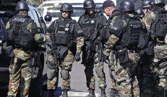 Swat team personnel gather for a briefing before entering the the former Roth's grocery store to investigate an armed robbery at School House Square in Keizer, Ore., on Tuesday, March 18, 2014.  A Brinks employee was robbed at gunpoint when he was servicing an ATM machine, said Keizer Police Deputy Chief Jeff Kuhns. (AP Photo/Statesman-Journal, Timothy J. Gonzalez)