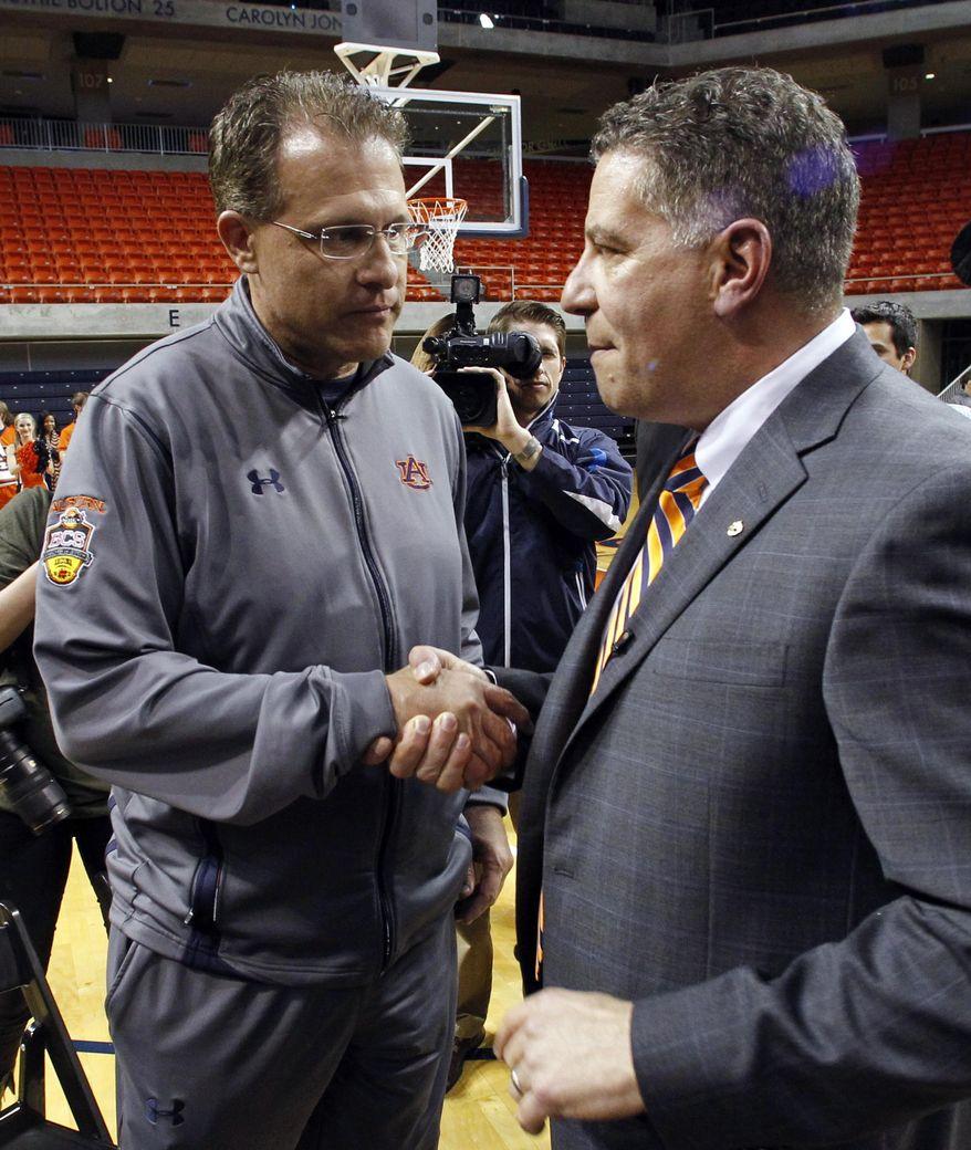 Auburn football coach Gus Malzahn, left, greets Bruce Pearl, who was named men's basketball coach at Auburn on Tuesday, March 18, 2014, in Auburn, Ala. (AP Photo/Butch Dill)
