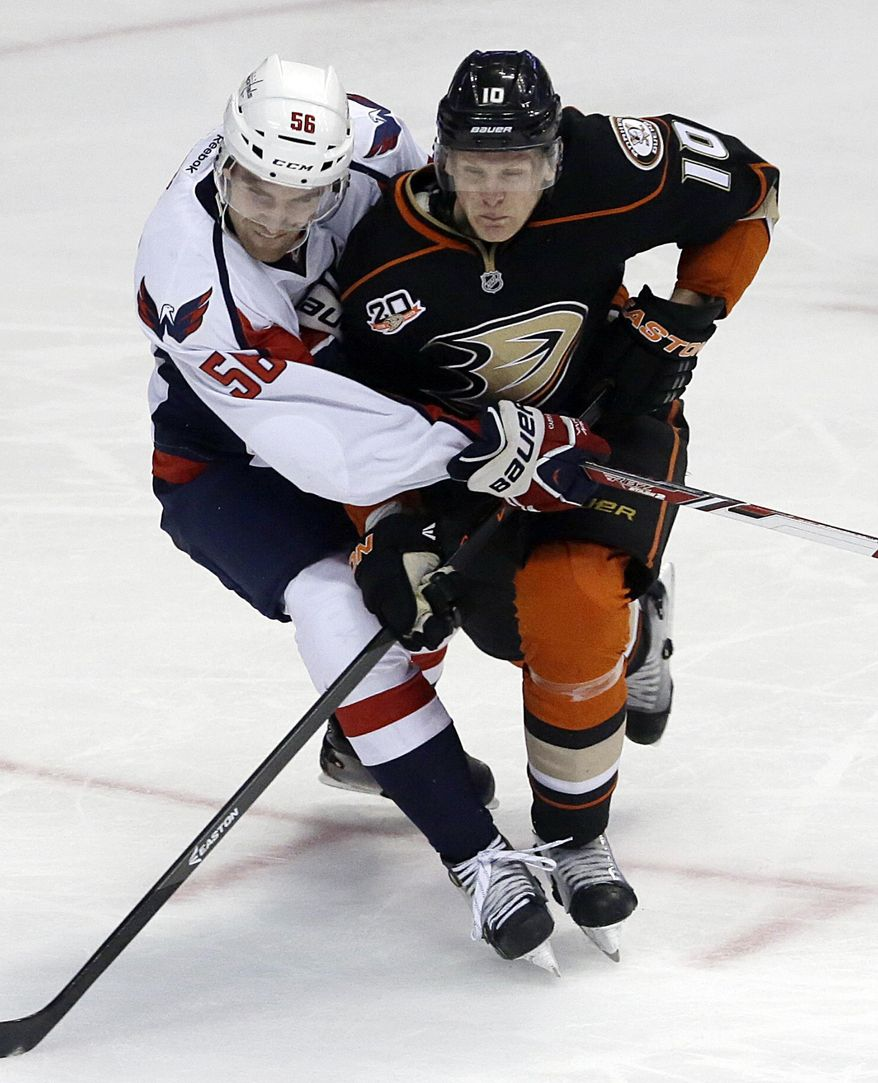 Anaheim Ducks right winger Corey Perry (10) and Washington Capitals defenseman Patrick Wey (56) tangle during the second period of an NHL hockey game Tuesday, March 18, 2014, in Anaheim, Calif. (AP Photo/Reed Saxon)