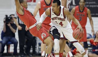St. Mary's guard Stephen Holt (14) tries to get around Utah guard Brandon Taylor (11) during the first half of an NCAA college basketball game against Utah in the first round of the National Invitational Tournament in Moraga, Calif., Tuesday, March 18, 2014. (AP Photo/Tony Avelar)