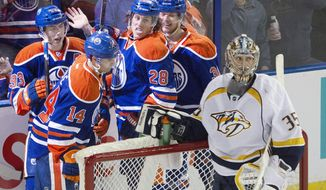 Nashville Predators goalie Pekka Rinne (35) looks on as Edmonton Oilers' Ryan Nugent-Hopkins (93), Jordan Eberle (14), Ryan Jones (28) and Philip Larsen (36) during the second period of an NHL hockey game Tuesday, March 18, 2014, in Edmonton, Alberta. (AP Photo/The Canadian Press, Jason Franson)