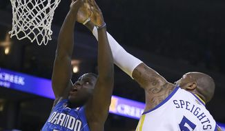 Orlando Magic's Victor Oladipo, left, lays up a shot against Golden State Warriors' Marreese Speights during the first half of an NBA basketball game Tuesday, March 18, 2014, in Oakland, Calif. (AP Photo/Ben Margot)
