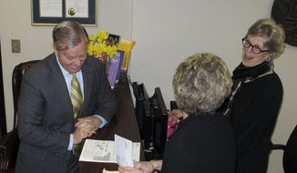 U.S. Sen. Lindsey Graham gives a check to the South Carolina election commission as he files to run for re-election on Wednesday, March 19, 2014, in Columbia, S.C. Graham is seeking a third tern, (AP Photo/Jeffrey Collins)