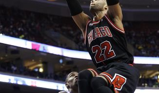 Chicago Bulls' Taj Gibson (22) dunks the ball past Philadelphia 76ers' Jarvis Varnado (40) during the first half of an NBA basketball game, Wednesday, March 19, 2014, in Philadelphia. (AP Photo/Matt Slocum)