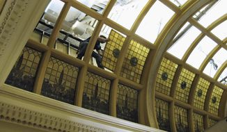 A repair crew member lifts a stained glass panel from a South Dakota Capitol skylight on March 19, 2014 in Pierre, S.D. The crew will remove 60 of the 90 panels in this skylight and restore them in a Wisconsin workshop. The glass will be reinstalled by the state's 125th anniversary.(AP Photo/Nora Hertel)