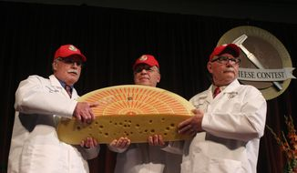Three judges for the 2014 World Championship Cheese Contest hold the champion, a Swiss Emmentaler, Wednesday, March 19, 2014, in Madison, Wis. Cheesemaker Gerard Sinnesberger from Kaserei Sinnesberger in Gams, Switzerland, took top honors out of 2,615 entries from 22 countries. (AP Photo/Carrie Antlfinger)