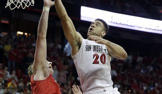 New Mexico's Cameron Bairstow, front left, covers a shot from San Diego State's JJ O'Brien during the second half of an NCAA college basketball game for the Mountain West Conference tournament championship on Saturday, March 15, 2014, in Las Vegas. New Mexico defeated San Diego State 64-58. (AP Photo/Isaac Brekken)