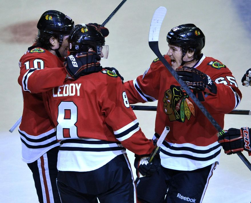 Chicago Blackhawks' Andrew Shaw (65), celebrates with teammates Nick Leddy (8), and Patrick Sharp (10), after scoring during the second period of an NHL hockey game against the St. Louis Blues in Chicago, Wednesday, March, 19, 2014. (AP Photo/Paul Beaty)