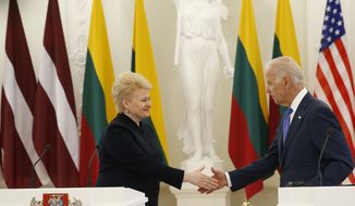 Vice President Joe Biden, right, shakes hands with  Lithuania's President Dalia Grybauskaite after giving a joint statement at the Presidential palace in Vilnius, Lithuania, Wednesday, March 19, 2014. Vice President Joe Biden has arrived in Lithuania to reassure Baltic leaders that the U.S. is committed to defending its NATO allies in the face of Russia's intervention in Crimea. (AP Photo/Mindaugas Kulbis)